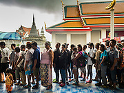 11 SEPTEMBER 2015 - BANGKOK, THAILAND:  People line up during a food distribution for poor members of the community at Wat Kalayanamit in the Thonburi section of Bangkok. Food distribution is a common way of making merit in Chinese Buddhist temples. Wat Kalayanamit, a Thai Theravada temple, was founded by a Chinese-Thai family in the 1820s and observes both Thai and Chinese Buddhist traditions. The food distribution was not related to the temple's efforts to evict people living on the temple grounds, but many of the people at the food distribution live in the houses the temple plans to raze.   PHOTO BY JACK KURTZ