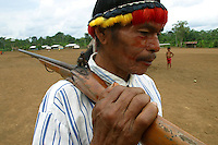 Antonio Wasump Samaraint, an indian elder of the Achuar tribe that is opposed to oil companies in the Amazon, walks with his carbine in the village of Pumpuentsa in Ecuador's Amazonian jungle.  Energy companies are expanding their operations into some of the world's last undisturbed ecosystems, searching for oil in the flat green forest of Ecuador's Amazon region.(Photo/Scott Dalton)