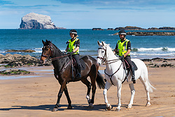 North Berwick, Scotland, UK. 26 April 2020. Mounted police patrolling the beaches of North Berwick in East Lothian this afternoon. Horses Inverness (dark) and Edinburgh travelled from their stables in Stewarton in Ayrshire for today's walk. However the beaches were very quiet and the horses' main duty was to pose for photographs with the few people outdoors. Pictured; Mounted police on beach with Bass Rock in the distance.  Iain Masterton/Alamy Live News
