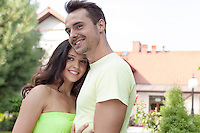 Smiling young couple embracing outdoors