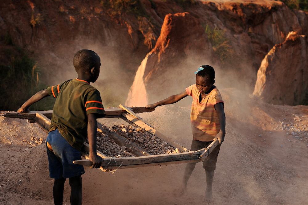 12-03-19   -- UGANDA --   l-r Viko Dodo, 6, and Ronny Komakech, 5, sift aggregate at a rock quarry in the Acholi Quarter on March 19. Since the early 1990's, people from the Acholi tribe (and from other northern tribes) migrated to a plot of land in a suburb of Kampala to escape the violence in the north. Now, rather than returning to their ancestral lands, some are calling the Acholi Quarter home. Many residents, unable to find well-paying employment, make a living mining and crushing rocks by hand. Photo by Daniel Hayduk