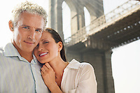 Couple embracing under Brooklyn Bridge portrait
