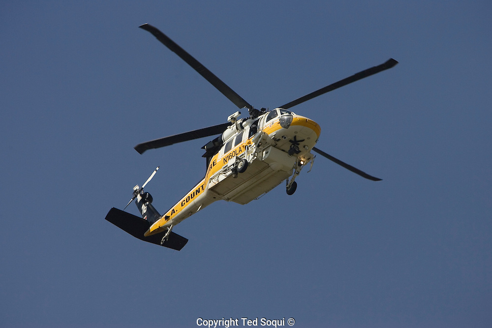 """A LA County Black Hawk helicopter flies over the Malibu Colony..Malibu wild fire..A brush fire that may have been sparked by downed power.lines swept across Malibu Canyon today, burning about 1,200 acres and destroying a church and several other structures in the beach-side community, including five homes..The fire was fed by high """"Santa Ana"""" type of winds which are very low in humidity and high in wind speed and dry out drought stricken vegetation..Wind speed were clocked at 60+ miles per hour."""