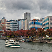 A dinner boat cruises past downtown Portland, OR on the Willamette River.