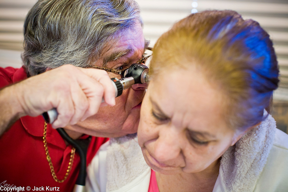 08 DECEMBER 2010 - PHOENIX, AZ: Dr. CHARLES LEVISON checks the MARIA URILLAS' ears during a visit to Mission of Mercy mobile clinic in Phoenix, AZ, Wednesday, Dec. 8. Mission of Mercy has been providing free medical help for people in the Phoenix area since 1997. In the last two years, as the Arizona economy continued its recessionary slide, patient load at the clinics has more than doubled. Mission of Mercy, which relies on voluntary medical help and financial donations, recently acquired another mobile clinic so they could expand their reach into suburban areas they previously had not served. Mission of Mercy has provided free medical help to more than 43,000 patients in the Phoenix area since 1997.  PHOTO BY JACK KURTZ