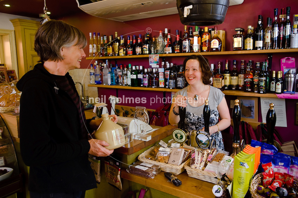 Louise Smith owner of the Jug & Bottle off licence and deli, with a customer, Bubwith village, East Yorkshire.