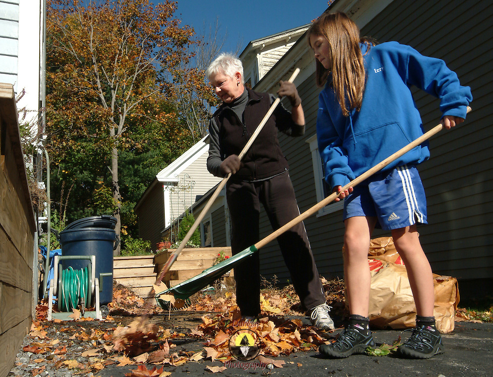 October 28, 2007 -- BATH, Maine.  Karen Bussey, left, of Bath works with her granddaughter, Isabelle Paulus, 9, on Sunday afternoon to clean leaves out of her garden after the Saturday's rain showers.  Photo by Roger S. Duncan.