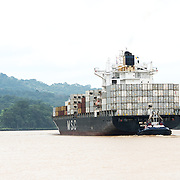 A tugboat helps a large container ship navigate a narrow section of the Panama Canal. Opened in 1914, the Panama Canal is a crucial shipping lane between the Atlantic and Pacific Oceans that mean that ships don't have to go around the bottom of South America or over the top of Canada. The Canal was originally built and owned by the United States but was handed back to Panama in 1999.
