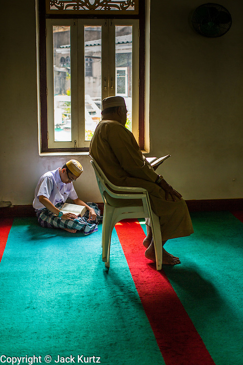 21 FEBRUARY 2013 - BANGKOK, THAILAND: A boy and man read the Koran in Haroon Mosque in Bangkok. Haroon Mosque, originally known as Masjid Ton Samrong, is one of the first mosques in Bangkok and was originally built in the middle of the 19th century. It was established by Musa Bafadel, an Indonesian trader from Pantiyanah, south of Borneo in what is now Indonesia. The mosque is now named after Haroon, Musa Bafadel's son who inherited his father's trade empire. The mosque was originally built of wood, but the wood decayed in Bangkok's climate and is now built of bricks and mortar. The wood was salvaged and used in the construction of the mosque.      PHOTO BY JACK KURTZ