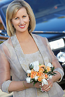 Middle-aged woman holding bouquet in front of limousine, portrait