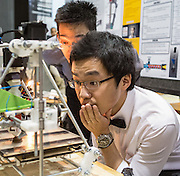 Qin Hu, right, and Edwin Li, left, anxiously watch their chocolate 3D printer in action at the Schulich School of Engineering Capstone Design Fair at the University of Calgary on Tuesday April 8, 2014. (Jenn Pierce/Calgary Herald)