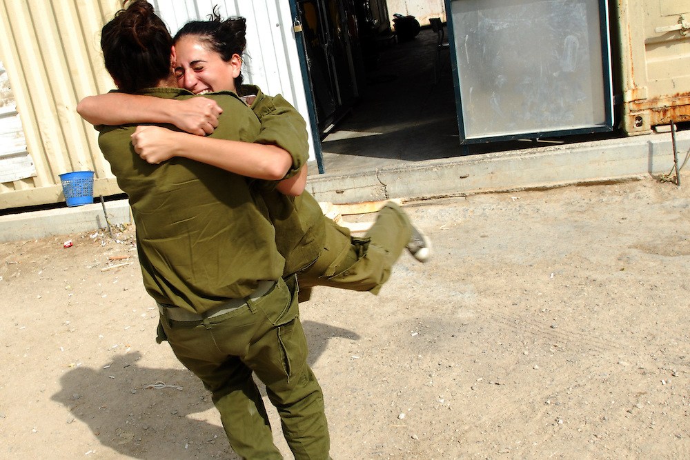 IDF woman reserve soldiers are hugging and playing in  an IDF outpost at South Mount Hebron, South of Israel. Following their active service, women, like men, are in theory required to serve up to one month annually in reserve duty. However, in practice only some women, mostly in combat roles, get called for active reserve duty, and only for a few years following their active service, with many exit points (e.g., pregnancy).