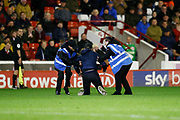 Stewards catch the pitch invader during the EFL Sky Bet Championship match between Barnsley and Derby County at Oakwell, Barnsley, England on 2 October 2019.