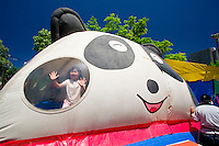 A young girl on an inflatable jumping castle in the shape of a panda at the annual Sapporo Matsuri festival in Nakajima Park, Sapporo, Hokkaido, Japan