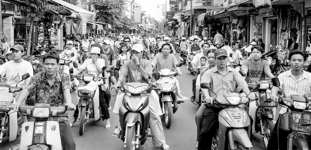 Large amounts of motorcycles stopped at a red light in Hanoi, 2003. Motorcycles are the preferred mean of transportation in Vietnam and trafic can get very dense.