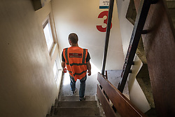© Licensed to London News Pictures. 11/08/2017. London, UK. A fire warden checks the 3rd floor of a tower block on the Ledbury Estate. Fire wardens have been in place on every other floor here on a 24 hour watch since the Grenfell fire tragedy in June. Residents on the Ledbury Estate in south London have been told they will have to leave their properties over the next few weeks. A structural survey carried out after the Grenfell fire found cracks that could lead to a collapse if a gas explosion occured in one of the flats. Photo credit: Peter Macdiarmid/LNP