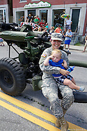 Tabitha Lord rides a Howitzer-like gun with son, Calem (17 mos) on her lap in the Waterbury 4th of July Parade on Saturday