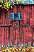 An neglecyed basketball hoop mounted on a rural red barn, New York, USA.