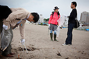 Tokyo -  May 29, 2010 - Konkatsu, the Japanese marriage Hunting. On Miura beach, 80 km from Tokyo, a konkatsu tour is organized for the participants who want to collect garbage on the beach. Kaori, 33 (C), chatting with a man.