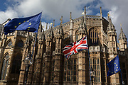 On the day that MPs in Parliament vote on a possible delay on Article 50 on EU Brexit negotiations by Prime Minister Theresa May, the EU flag and the British Union Jack fly in front of Westminster Abbey during a Brexit protest opposite Parliament, on 14th March 2019, in Westminster, London, England.