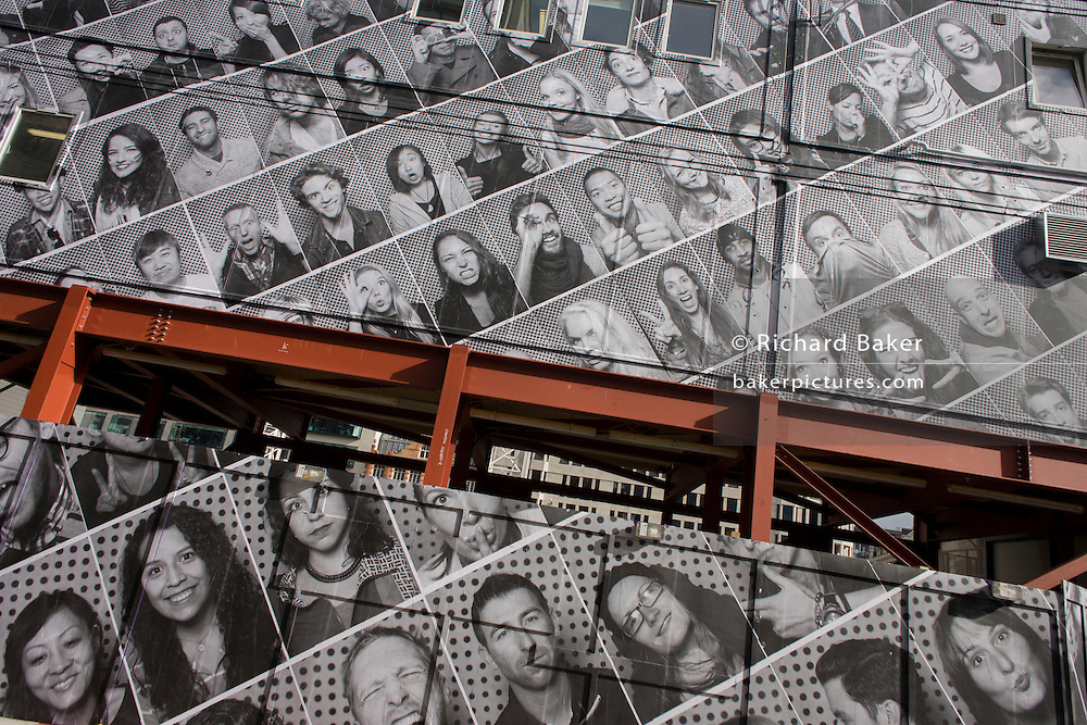 Makeshift girder for a site office and a construction hoarding featuring dozens of London faces in the City.