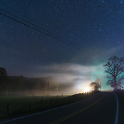 Lights from a house are illuminated in fog that blankets Browns Creek road under a starry sky in Pocahontas County, West Virginia.