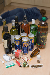 Selection of drugs and alcohol on the table with beaten woman lying on the floor,