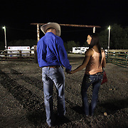 "Dustin Smith, a cowboy from St. Paul, is consoled by his girlfriend Whitney Richey after being bucked off a bull in his hometown rodeo before driving quickly to Molalla for the late-night Molalla Buckeroo. Known as ""Cowboy Christmas,"" the time around the Fourth of July is packed with rodeos throughout the West, and many cowboys try to compete in as many as possible."