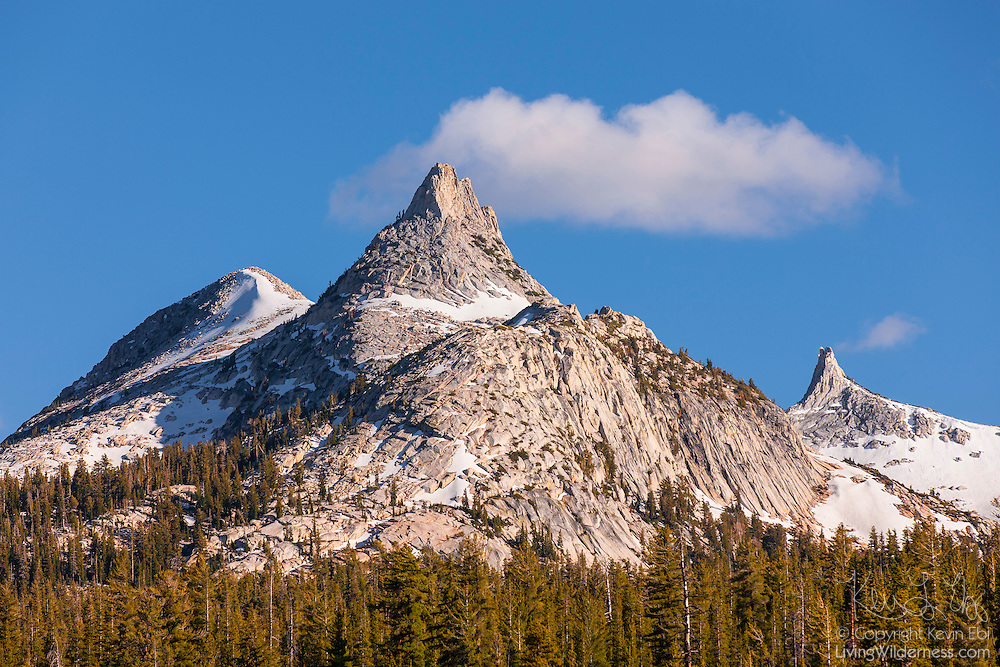 A cumulus cloud seems to emerge from the summit of Unicorn Peak, a 10,823 foot (3299 meter) peak in Yosemite National Park, California. While the peak has three summits, it appears as a single spire from narrow angles in the Tuolumne Meadows. Cockscomb, a 11,065 foot (3373 meter) peak also in the Cathedral Range, is visible to the right of Unicorn Peak.
