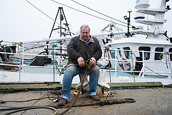 © Licensed to London News Pictures. 03/04/2014<br /> <br /> Whitby, North Yorkshire, United Kingdom<br /> <br /> Fisherman Richard Brewer, skipper of the fishing boat Copious, sits on the dock side and fixes ropes on a foggy morning in the North Yorkshire seaside town of Whitby. Richard is a fifth generation fisherman and runs the last remaining registered fishing boat of this type out of Whitby. <br /> <br /> Photo credit : Ian Forsyth/LNP