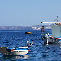 Fishing boats in the pristine waters of the Greek Cyclades - Tholos island, Santorini.