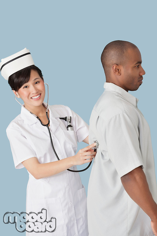 Portrait of a happy female doctor examining male patient's back with stethoscope over light blue background