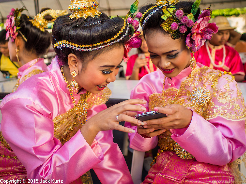 "14 JANUARY 2015 - BANGKOK, THAILAND: Girls in traditional attire look at pictures on a smart phone before the 2015 Discover Thainess parade. The Tourism Authority of Thailand (TAT) sponsored the opening ceremony of the ""2015 Discover Thainess"" Campaign with a 3.5-kilometre parade through central Bangkok. The parade featured cultural shows from several parts of Thailand. Part of the ""2015 Discover Thainess"" campaign is a showcase of Thailand's culture and natural heritage and is divided into five categories that match the major regions of Thailand – Central Region, North, Northeast, East and South.     PHOTO BY JACK KURTZ"