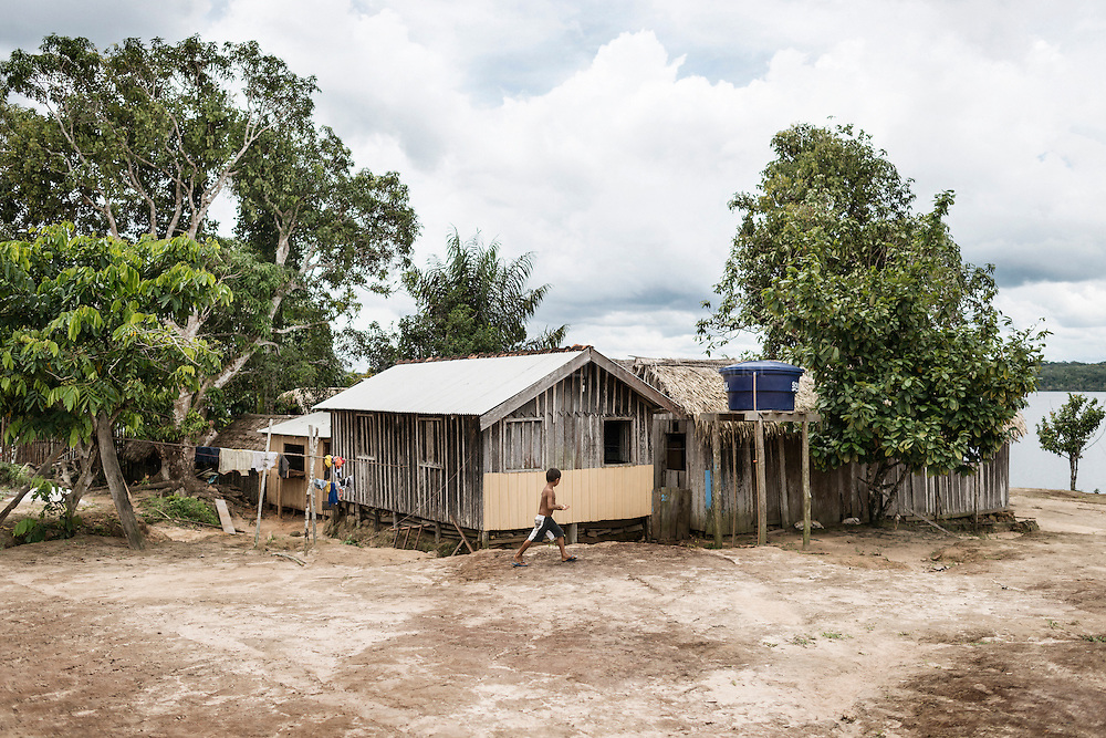 """In their """"Sitios"""" families build their kitchen halfway between the house and the river, where the men roast guarana and the women prepare meals from manioc root. They also have their dock where the family members bathe, wash clothes, soak cassava, wash guarana and land their canoes."""