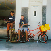 Teenage boy sitting on the back of a delivery bicycle another boy rests his foot on a crate of fruit Brazil
