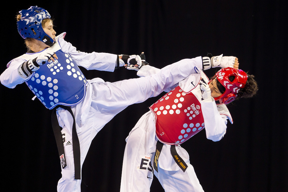 Celina Proffen (L) of Argentina kicks Vanessa Vasquez of El Salvador during their repechage contest in the women's Taekwondo -57kg division of at the 2015 Pan American Games in Toronto, Canada, July 20,  2015.  AFP PHOTO/GEOFF ROBINS
