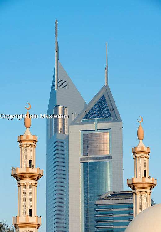 Emirates Towers framed between mosque minarets and skyline of skyscrapers in Dubai United Arab Emirates UAE