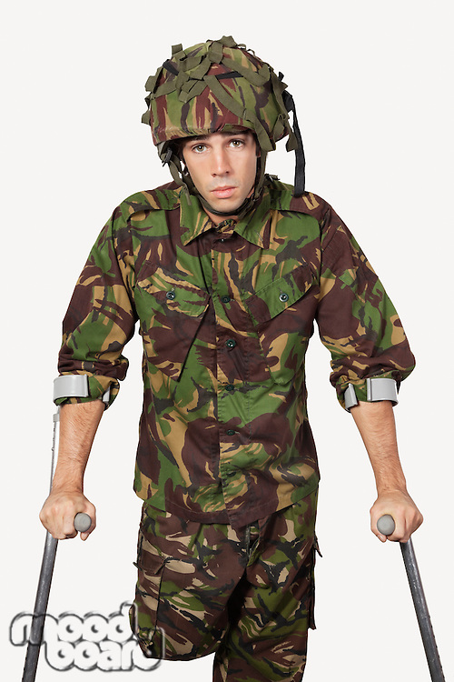 Portrait of young soldier holding crutches against gray background