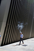 A man exhales vape smoke while walking along a street in the City of London, the capital's financial district (aka the Square Mile), on 10th July 2019, in London England.