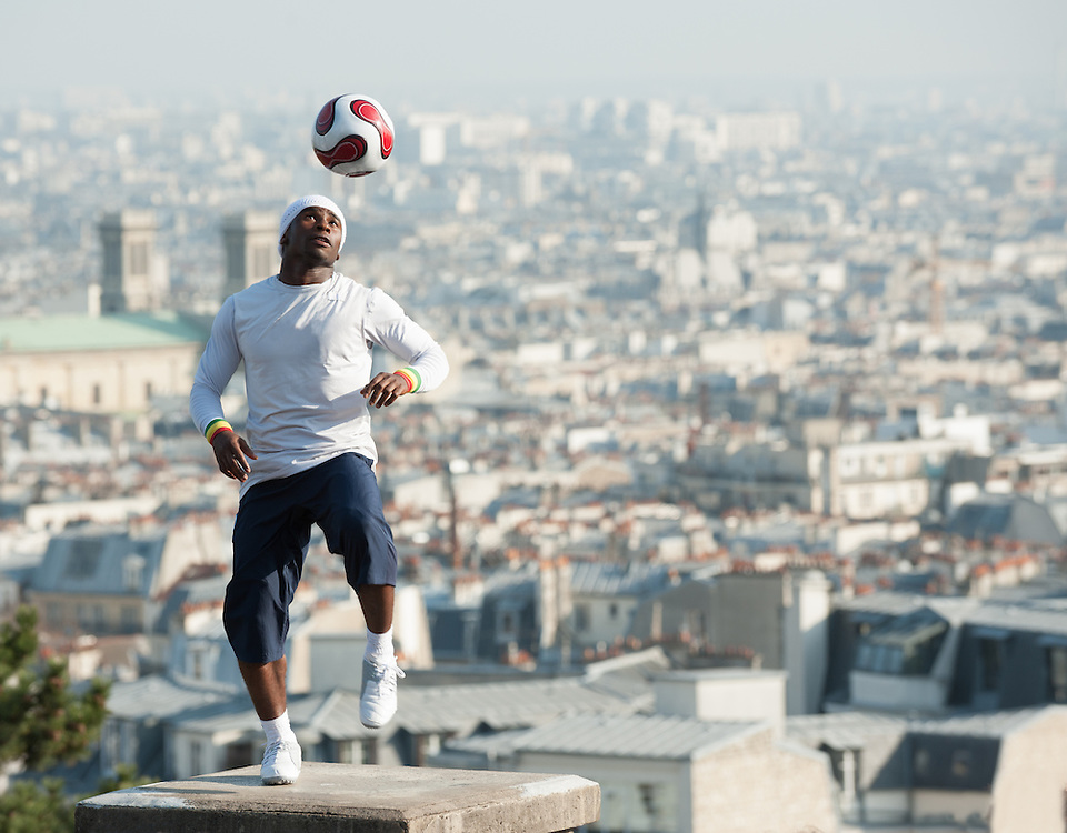 Football freestyler playing on a pillar above city