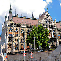 West Façade of Parliament Building in Budapest, Hungary  <br /> The exterior of the Parliament Building is profound but the interior is remarkable. The building has nearly 700 rooms. During your tour, you will be impressed with the ornate staircase, the assembly halls plus the frescos, mosaics and stained-glass windows. Most exciting is seeing the crown jewels including the Holy Crown of Hungary. Tours are suspended when the National Assembly is in session, so check the website for availability.