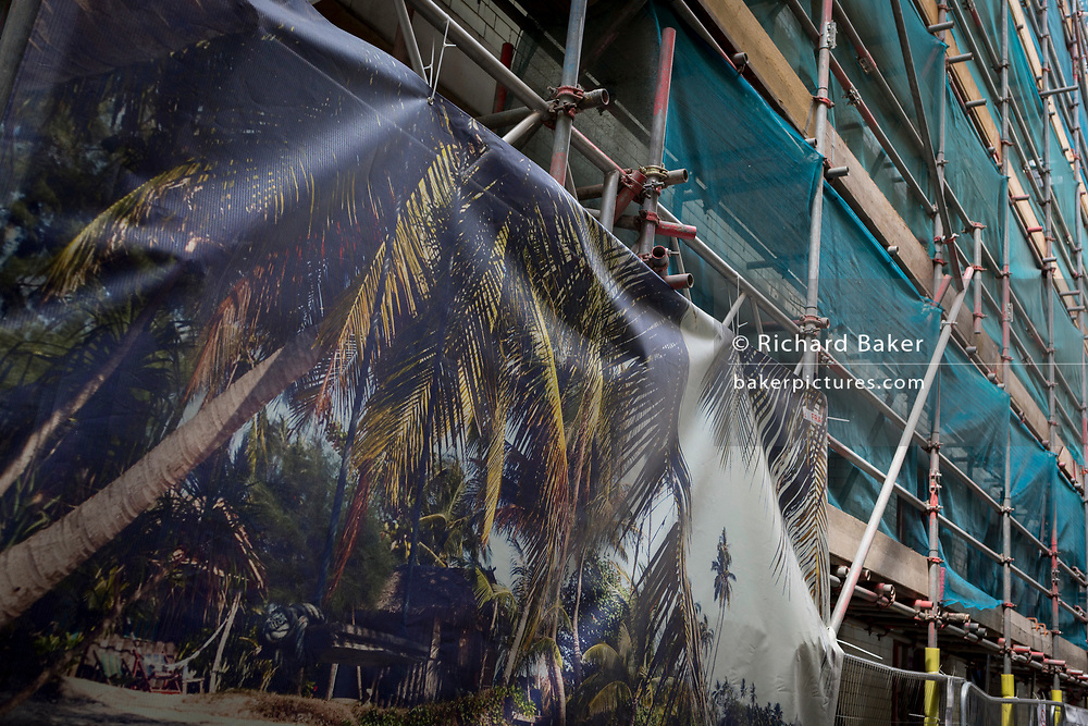 A poster showing a tropical paradise and construction scaffolding in the West End, on 11th July 2018, in London, England.