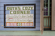 sign with frame around it on side of building advertising Ruth's Cozy Corner; Ursulines Street residence
