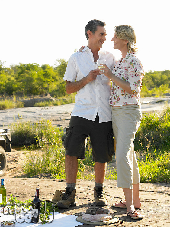 Couple on picnic toasting looking in eyes smiling