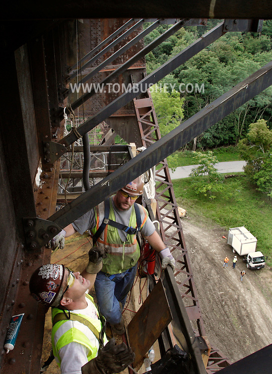 An ironworker on a platform hung under the tracks of the Moodna Viaduct railroad trestle talks to a supervisor standing on the platform on Tuesday, Aug. 9, 2011.  Metro North is repairing and repainting steel sections on the open deck girder bridge. The structure, first opened for rail traffic in 1909, is the highest railroad trestle east of the Mississippi.