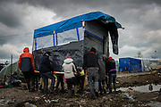 Refugees and volunteers work together to move makeshift shelters in the Calais refugee camp known as the 'Jungle' on January 13, 2016 following a deadline given by the French police to clear the area within 100 metres of the highway.