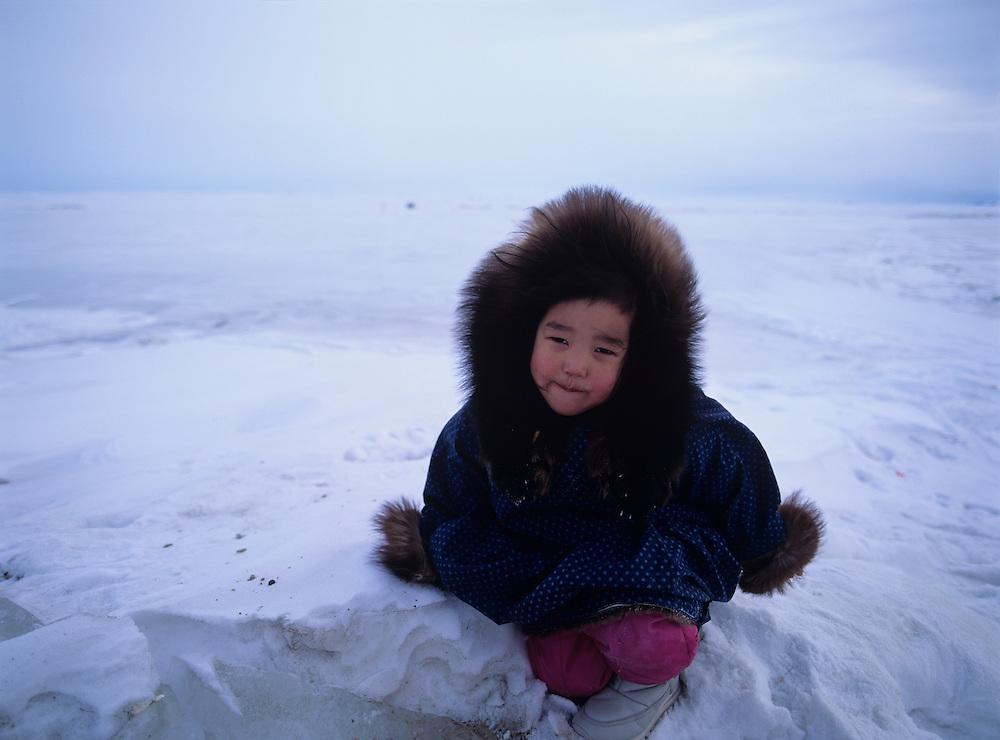USA, Alaska, Well-bundled Eskimo girl waits for Iditarod mushers on Norton Sound near village of Koyuk