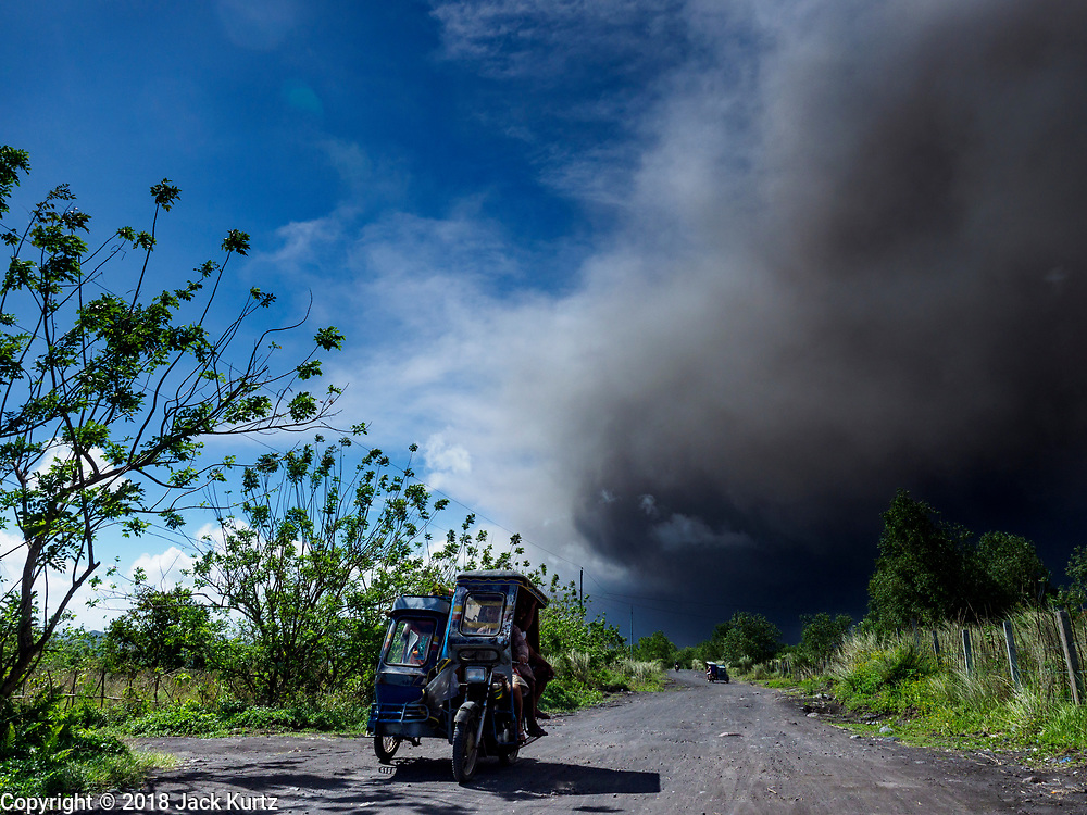 "22 JANUARY 2018 - CAMALIG, ALBAY, PHILIPPINES: People ride a Filipino tricycle taxi while they leave their communities on the slopes of the Mayon volcano. There were a series of eruptions on the Mayon volcano near Legazpi Monday. The eruptions started Sunday night and continued through the day. At about midday the volcano sent a plume of ash and smoke towering over Camalig, the largest municipality near the volcano. The Philippine Institute of Volcanology and Seismology (PHIVOLCS) extended the six kilometer danger zone to eight kilometers and raised the alert level from three to four. This is the first time the alert level has been at four since 2009. A level four alert means a ""Hazardous Eruption is Imminent"" and there is ""intense unrest"" in the volcano. The Mayon volcano is the most active volcano in the Philippines. Sunday and Monday's eruptions caused ash falls in several communities but there were no known injuries.    PHOTO BY JACK KURTZ"