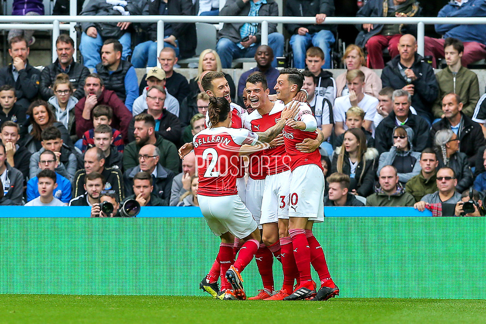 Granit Xhaka (#34) of Arsenal celebrates Arsenal's first goal (0-1) with Mesut Ozil (#10) of Arsenal and Hector Bellerin (#2) of Arsenal during the Premier League match between Newcastle United and Arsenal at St. James's Park, Newcastle, England on 15 September 2018.
