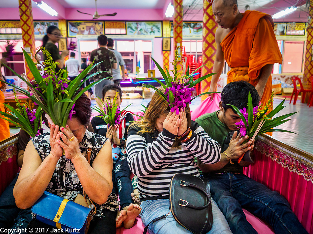 """29 MARCH 2017 - BANG KRUAI, NONTHABURI, THAILAND: A family sits up in a coffin representing their rebirth during a """"Resurrection Ceremony"""" at Wat Ta Kien (also spelled Wat Tahkian), a Buddhist temple in the suburbs of Bangkok. People go to the temple to participate in a """"Resurrection Ceremony."""" Groups of people meet and pray with the temple's Buddhist monks. Then they lie in coffins, the monks pull a pink sheet over them, symbolizing their ritualistic death. The sheet is then pulled back, and people sit up in the coffin, symbolizing their ritualist rebirth. The ceremony is supposed to expunge bad karma and bad luck from a person's life and also get people used to the idea of the inevitability of death. Most times, one person lays in one coffin, but there is family sized coffin that can accommodate up to six people. The temple has been doing the resurrection ceremonies for about nine years.          PHOTO BY JACK KURTZ"""